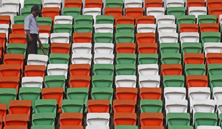 A security guard uses a broom to clean seats on the grandstand at the Buddh International Circuit in Greater Noida, on the outskirts of Delhi, India. (Vivek Prakash/Reuters)