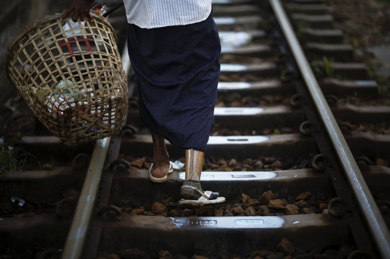 A man with a wooden leg cleans rubbish from the tracks of a circular train in Yangon's suburbs. Around Yangon, with its growing and increasingly demanding population of almost five million, a circular train operates, moving passengers through its suburbs. On a three hour long ride, a train made of rusted vehicles marked with different classes but little visible difference between them, takes passengers around the city stopping briefly at numerous small stations. As Myanmar opens up, the most immediate physical changes are on its streets, as new cars begin plying roads long dominated by rattletrap buses and rusting taxies. Barely changed since the British colonial era in the early 20th century, some of the decades-old buses and trains are starting to be retired. (Damir Sagolj/Reuters)