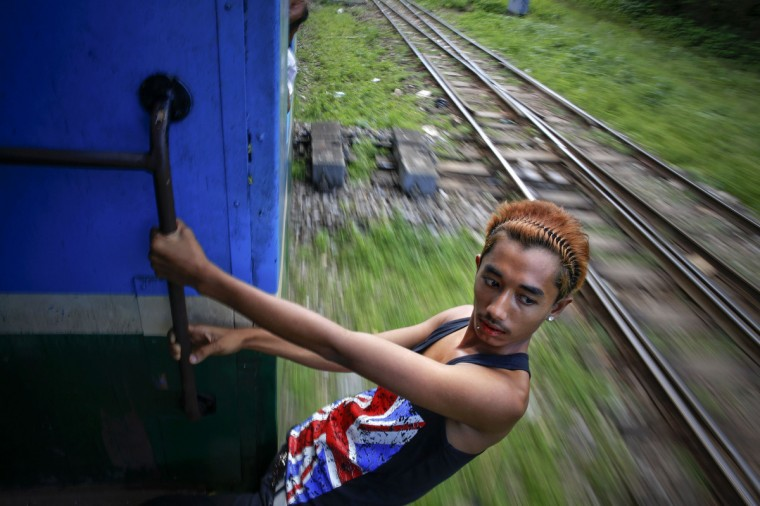 A young man hangs from a moving train in Yangon's suburbs. Around Yangon, with its growing and increasingly demanding population of almost five million, a circular train operates, moving passengers through its suburbs. On a three hour long ride, a train made of rusted vehicles marked with different classes but little visible difference between them, takes passengers around the city stopping briefly at numerous small stations. As Myanmar opens up, the most immediate physical changes are on its streets, as new cars begin plying roads long dominated by rattletrap buses and rusting taxies. Barely changed since the British colonial era in the early 20th century, some of the decades-old buses and trains are starting to be retired. (Damir Sagolj/Reuters)