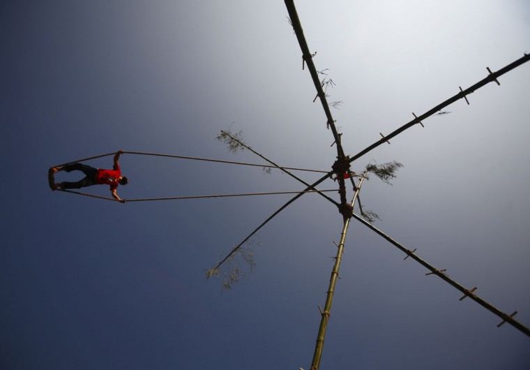 A Nepalese youth plays on a swing during the first day of Dashain, Hinduism's biggest religious festival, in Kathmandu. (Navesh Chitrakar/Reuters)