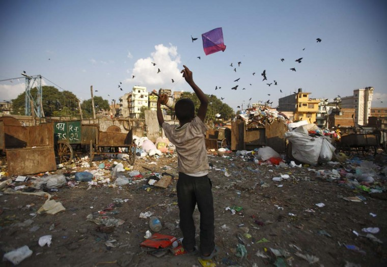 Iqbal Mohamed, 10, flies a kite as crows fly above a dumping site at the bank of Bishnumati River in Kathmandu October 15, 2012. (Navesh Chitrakar/Reuters)