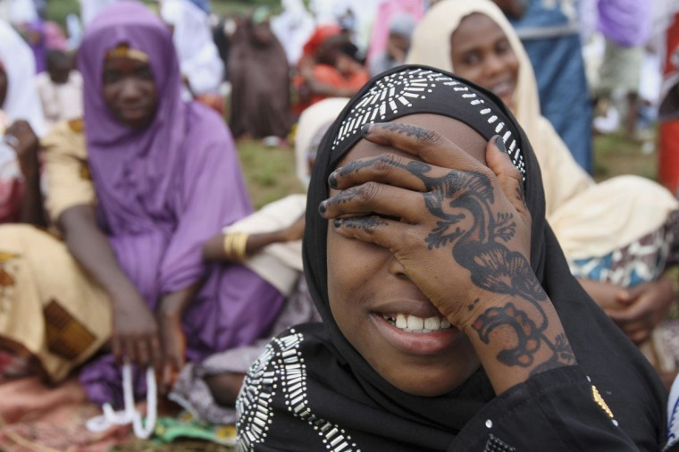 A girl covers her face as she waits for the start of Eid al-Adha prayers in Lagos. Muslims around the world celebrate Eid-al-Adha to mark the end of the Haj by slaughtering sheep, goats, cows and camels to commemorate Prophet Abraham's willingness to sacrifice his son Ismail on God's command. (Akintunde Akinleye/Reuters)