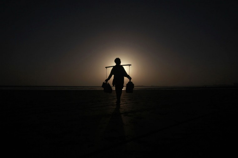 Rahmet Gul, 20, is silhouetted against the setting sun as he waits to sell green tea to customers along Karachi's Clifton beach in Pakistan. (Athar Hussain/Reuters)