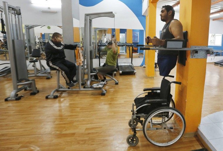 Wheelchair-bound Palestinian freelance photographer Moamen Qreiqea exercises in a gym in Gaza City October 1, 2012. Qreiqea, 25, lost both his legs in an Israeli air strike in 2008 while taking pictures east of Gaza. The father of two is determined to continue his career despite his disability. (Suhaib Salem/Reuters)