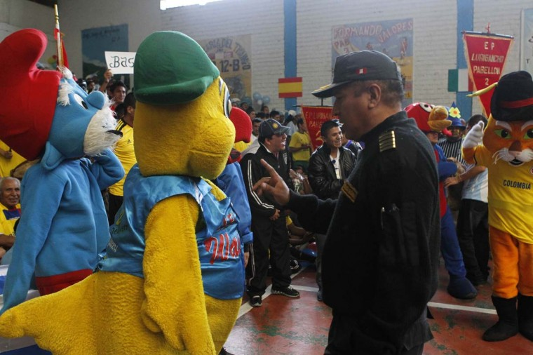A police officer talks to an inmate dressed as an Olympic team mascot during a sports event at the Lurigancho prison in Lima. Although Lurigancho prison is one of the most overcrowded, violent, and unruly jails in Latin America, its more than 8,500 prisoners live with so much freedom inside the walled perimeter that they have created their own city, which mimics the urban society on the outside. Picture taken September 10, 2012. (Mariana Bazo/Reuters)