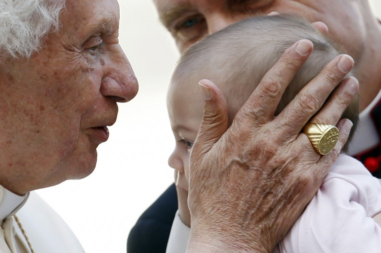Pope Benedict XVI kisses a baby as his principal private secretary Monsignor Georg Gaenswein (rear) smiles after the Wednesday general audience in Saint Peter's square, at the Vatican. (Giampiero Sposito/Reuters)
