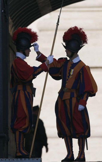 A Swiss guard adjusts the helmet on another Swiss guard before the arrival of Pope Benedict XVI to conduct a mass to open the year of faith at the Vatican. (Stefano Rellandini/Reuters photo)