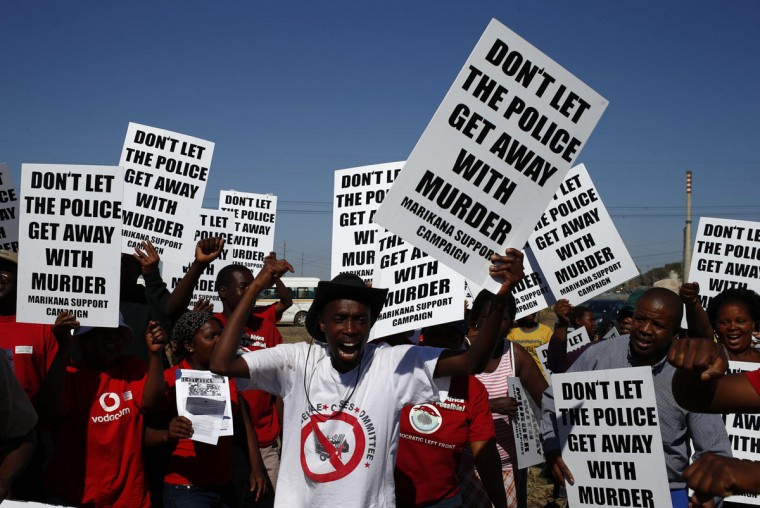 Demonstrators wave placards during a site inspection by the judicial commission of inquiry into the shootings at Lonmin's Marikana mine October 1, 2012. (Mike Hutchings/Reuters)