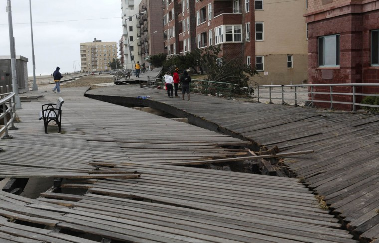 Pedestrians walk along a damaged section of a boardwalk in the borough of Queens in New York. The U.S. Northeast began crawling back to normal on Wednesday after monster storm Sandy crippled transportation, knocked out pwoer for millions and killed at least 45 people in nine states. (Gil Cohen Magen/Reuters)
