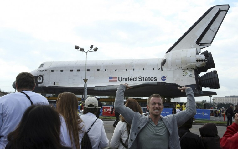 Joseph Duffield, 26, of Venice, seems to hold up the space shuttle Endeavour which was parked at the Drollinger's parking lot in Westchester, California. (Genaro Molina/Reuters)