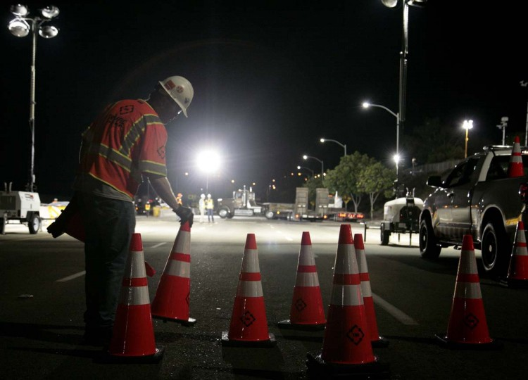 A worker lays traffic cones on Lincoln Boulevard outside Los Angeles International Airport, as roads are closed to move space shuttle Endeavour to the California Science Center in Los Angeles. Endeavour will nose out of the airport at about 2 a.m. on Friday as it begins a two-day ground journey atop a massive wheeled transporter to its final resting place at the science center on the edge of downtown. (Jason Redmond/Reuters photo)