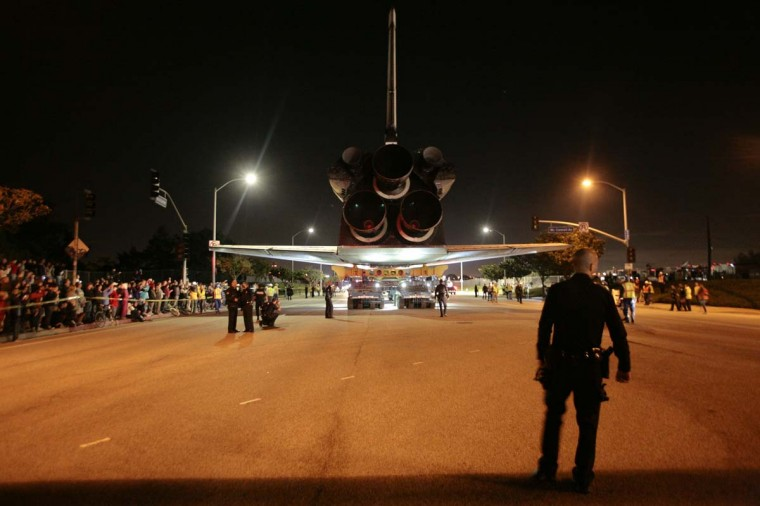 A police officer stands near space shuttle Endeavour as it leaves Los Angeles International Airport and is transported on city streets to the California Science Center in Los Angeles, California. (Jason Redmond/Reuters photo)