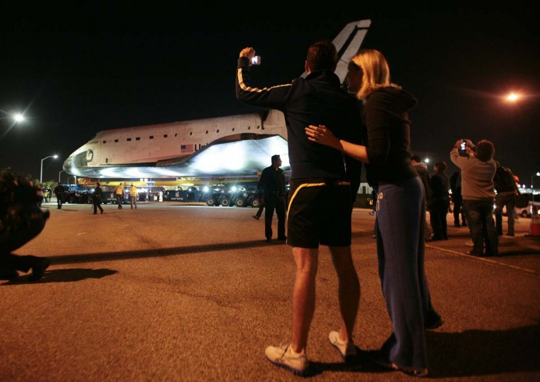 A couple watches as space shuttle Endeavour leaves Los Angeles International Airport and is transported on city streets to the California Science Center in Los Angeles, California October 12, 2012. Endeavour on Friday began a two-day ground journey atop a massive wheeled transporter to its final resting place at the science center on the edge of downtown. (Jason Redmond/Reuters photo)