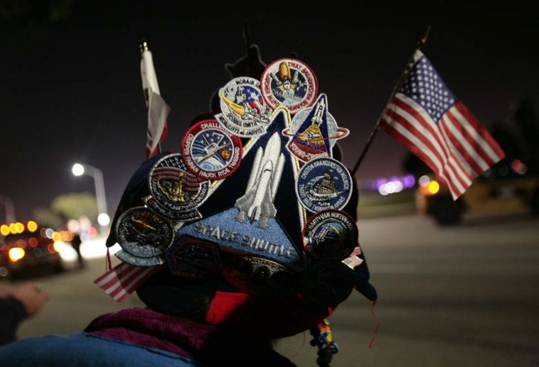 Vivianne Robinson of Santa Monica, California wears a hat with patches from various space shuttle missions as she watches space shuttle Endeavour make its way on city streets to the California Science Center in Los Angeles, California. (Jason Redmond/Reuters photo)