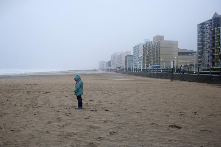 A beachgoer along the oceanfront observes the effects of high wind and heavy rain as Hurricane Sandy begins to arrive in Virginia Beach, Virginia. (Rich-Joseph Facun/Reuters)