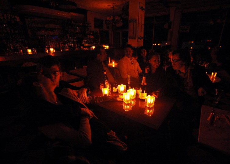 Customers and staff ride out Hurricane Sandy together by candle light at the Greenwich Village restaurant French Roast in New York. New York Power Company Consolidated Edison Inc. said that it had shut off power to part of Lower Manhattan to protect electrical equipment and to allow for quicker restoration after Hurricane Sandy passes. (Brendan McDermid/Reuters)