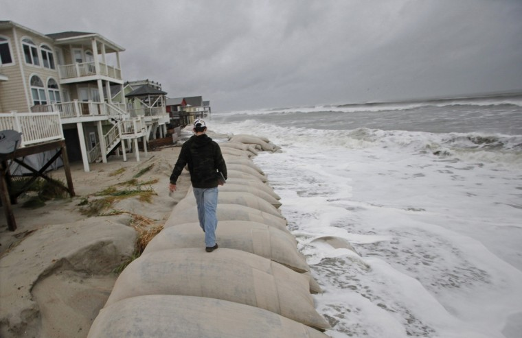 Cage Deal, a senior at Whiteville High School, walks to get a better vantage point as he gets video footage of the waves of Hurricane Sandy in Ocean Isle Beach, North Carolina. He drove the hour inland for a school project on weather. Hurricane Sandy is expected to make landfall on the Eastern Seaboard October 30, with direct impacts expected for the Mid-Atlantic or Northeast U.S. (Randall Hill/Reuters)