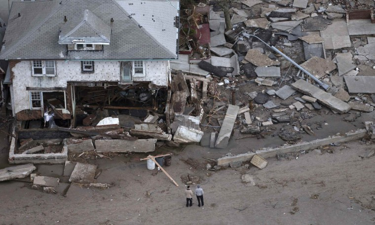 Men stand near a destroyed home in Seagate, New York. (Adrees Latif/Reuters)