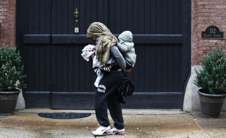 October 29, 2012: A woman carrying two children tries to reach home during rainfall in Jersey City, as Hurricane Sandy approaches New Jersey. (Eduardo Munoz/Reuters)
