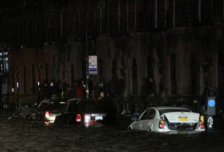 Flood waters brought on by Hurricane Sandy over run cars in New York's lower east side. Hurricane Sandy began battering the U.S. East Coast on Monday with fierce winds and driving rain, as the monster storm shut down transportation, shuttered businesses and sent thousands scrambling for higher ground hours before the worst was due to strike.(Brendan McDermid/Reuters)