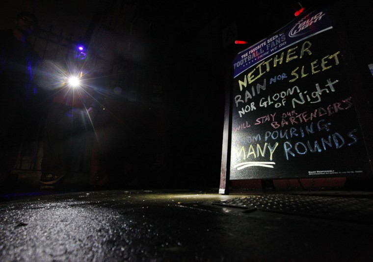 Manager Devin Vilardi stands with a flashlight outside Professor Thom's bar, which was still serving drinks to New Yorkers despite not having power due to the aftermath of Hurricane Sandy. (Brendan McDermid/Reuters)