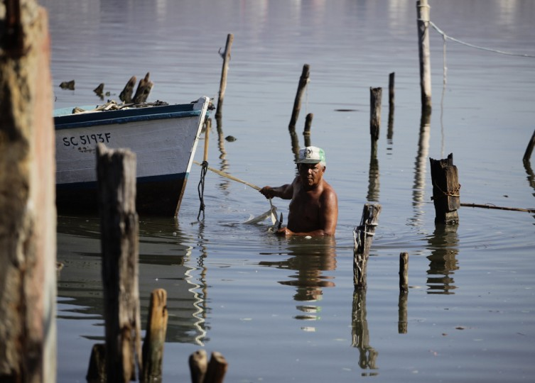 A fisherman pulls his boat at a destroyed dock after Hurricane Sandy passed through in Santiago de Cuba. Eleven people died in Cuba due to the storm, largely because of collapsed buildings, officials said. (Desmond Boylan/Reuters)