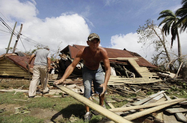 A man salvages planks from his damaged house after Hurricane Sandy hit Santiago de Cuba. The Cuban government said on Thursday night that 11 people died when the storm barreled across the island, most killed by falling trees or in building collapses in Santiago de Cuba province and neighboring Guantanamo province. (Desmond Boylan/Reuters)