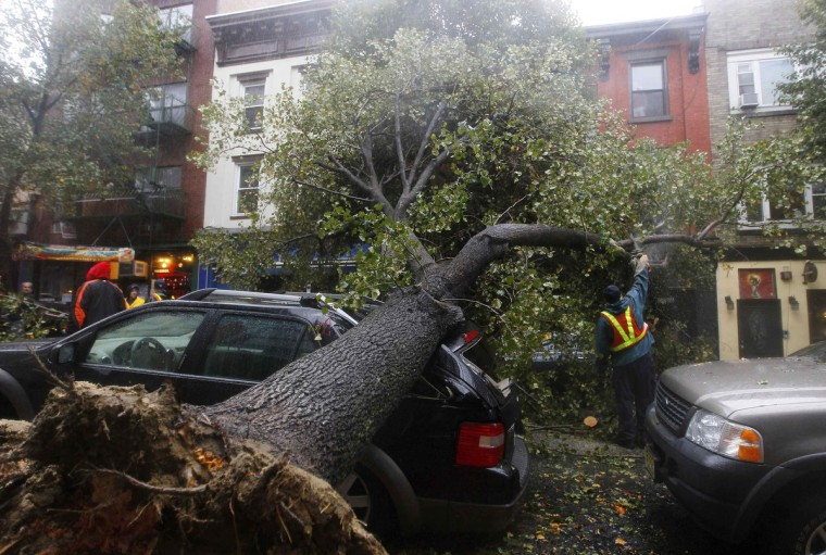 A workman cuts a tree in pieces after it fell on top of a car in Hoboken, New Jersey. Hurricane Sandy, one of the biggest storms ever to hit the United States, battered the densely populated East Coast, shutting down transportation, forcing evacuations in flood-prone areas and interrupting the presidential election campaign. (Gary Hershorn/Reuters)
