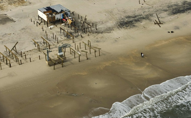 Two beach goers walk along the shoreline where a damaged home remains among pilings from a washed-out boardwalk, after Hurricane Sandy came ashore in Lavallette, New Jersey. (Steve Nesius/Reuters)