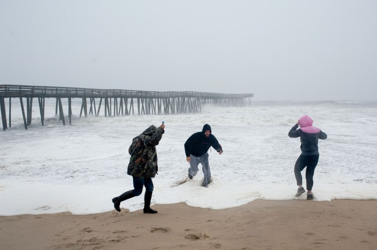 Beachgoers along the oceanfront get soaked by an incoming wave as Hurricane Sandy begins to arrive in Virginia Beach, Virginia. (Rich-Joseph Facun/Reuters)