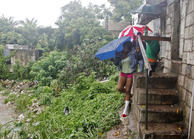 October 24, 2012: Jamaicans shelter themselves from the rain of approaching Hurricane Sandy as they walk along Sandy Park Gully in Kingston. (Gilbert Bellamy/Reuters)