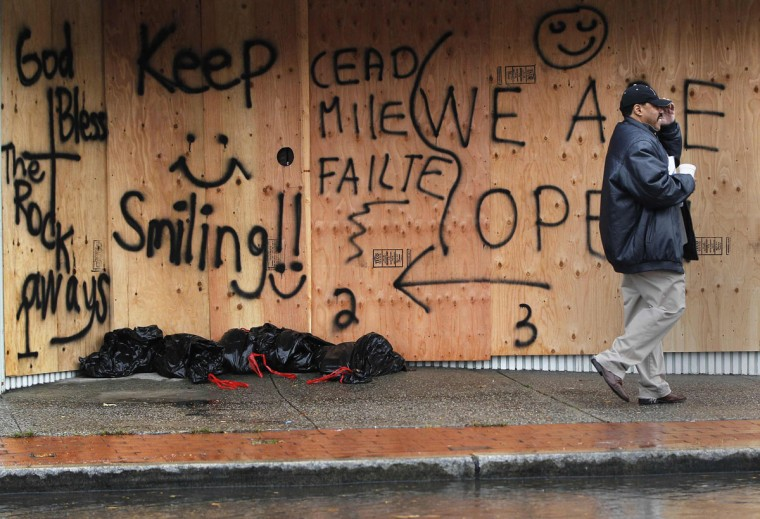 October 29, 2012: A man walks by a boarded up storefront in the Rockaways section of the Queens borough of New York. (Shannon Stapleton/Reuters)