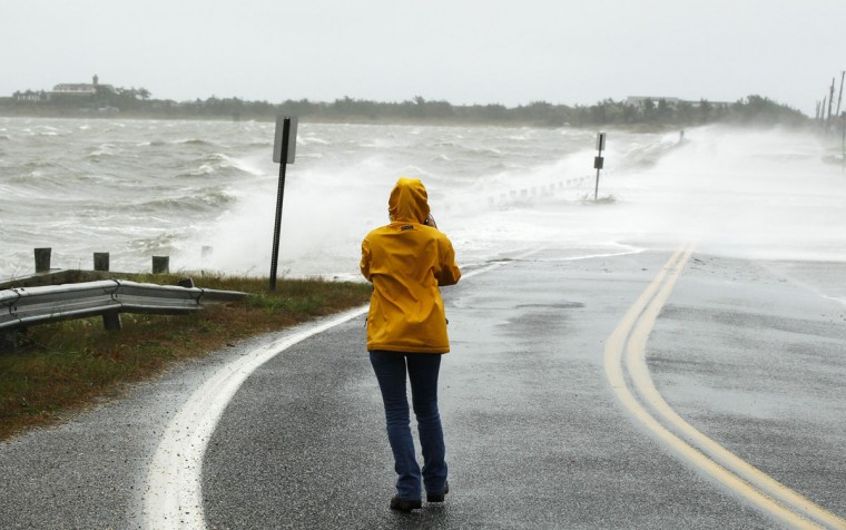 October 29, 2012: A woman takes photographs of waves pushed over a road by Hurricane Sandy in Southampton, New York. (Lucas Jackson/Reuters)