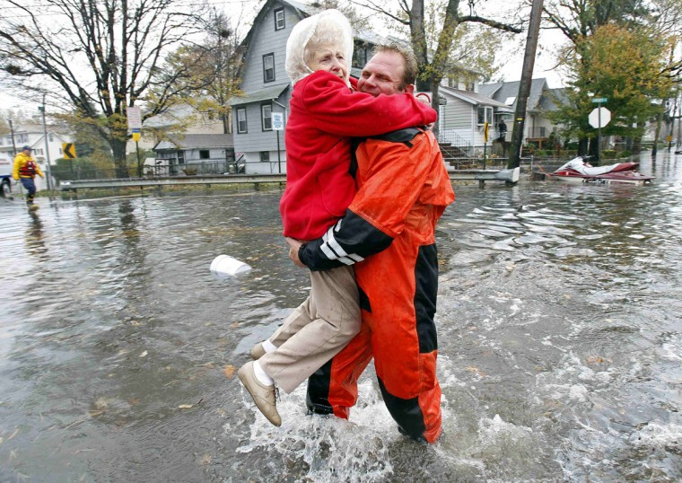 October 30, 2012: An emergency personnel carries an elderly resident from flood waters brought on by Hurricane Sandy in Little Ferry, New Jersey. (Adam Hunger/Reuters)
