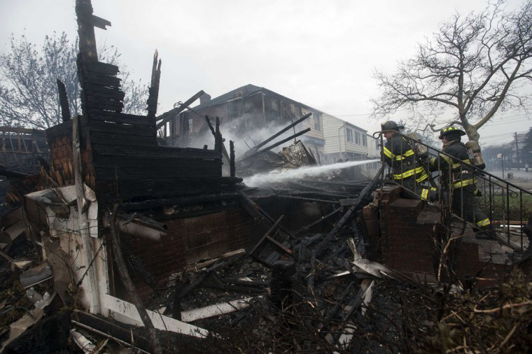 October 30, 2012: Firefighters work to extinguish a fire in the Rockaways section of New York. (Keith Bedford/Reuters)