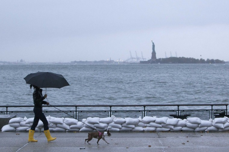 October 29, 2012: A woman walks her dog by sandbags in Battery Park in downtown Manhattan as Hurricane Sandy made its approach in New York. (Andrew Kelly/Reuters)