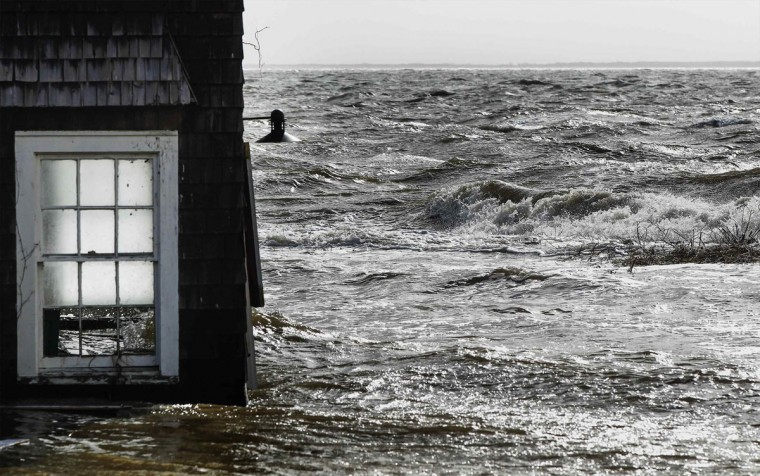 October 30, 2012: Water pushed up by Hurricane Sandy splashes into the window of a building standing by the shore in Bellport, New York. (Lucas Jackson/Reuters)