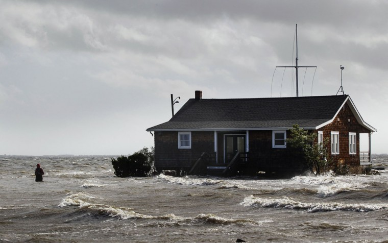 October 30, 2012: A man walks away from a building that has been surrounded by water pushed up by Hurricane Sandy in Bellport, New York. (Lucas Jackson/Reuters)