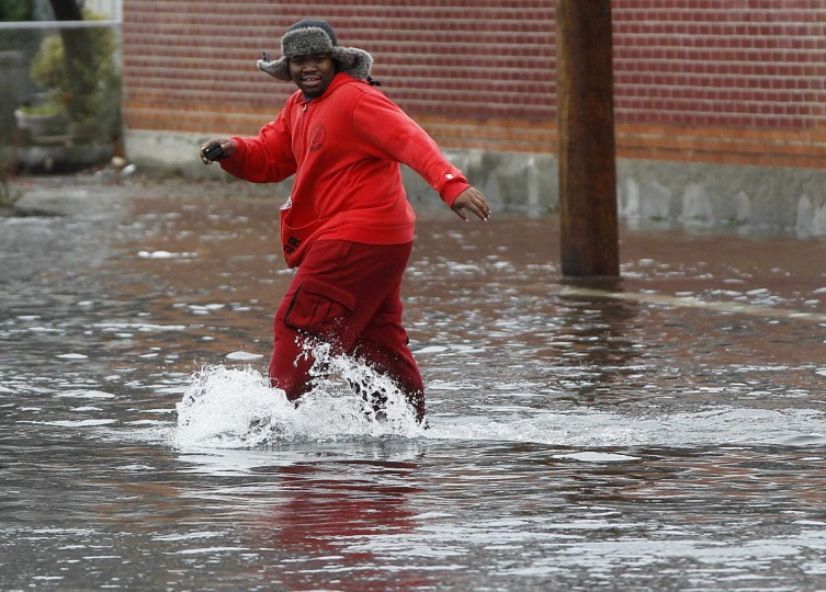 October 29, 2012: A man makes his way across a flooded Seagirt avenue in the borough of Queens in New York. (Shannon Stapleton/Reuters)