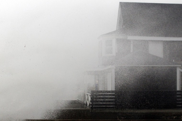 October 29, 2012: A wave crashes onto a house before the arrival of Hurricane Sandy in Scituate, Massachusetts. (Jessica Rinaldi/Reuters)