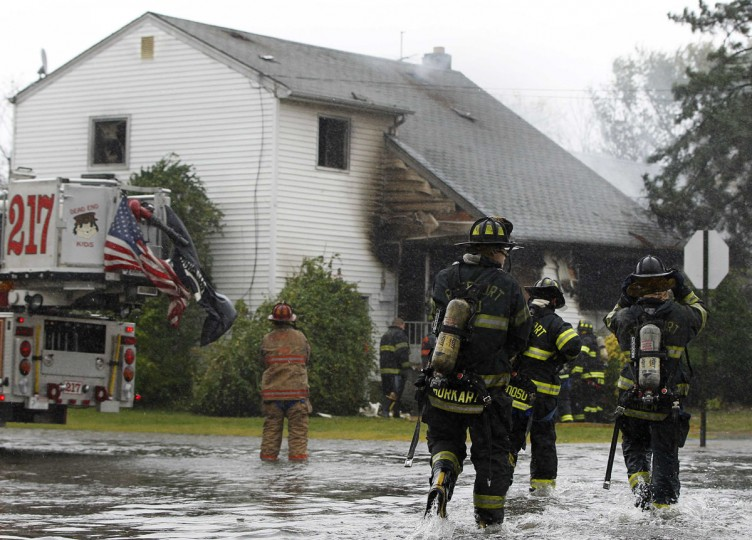 October 29, 2012: Members of the Freeport Fire Department respond to a house fire down a flooded street in Freeport, New York. (Shannon Stapleton/Reuters)