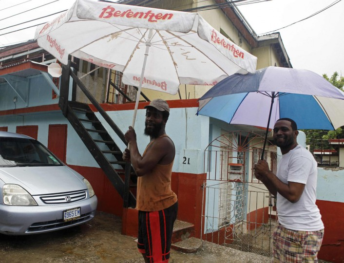 October 24, 2012: Jamaicans shelter themselves from the rain of approaching Hurricane Sandy in Kingston. (/Gilbert Bellamy/Reuters)