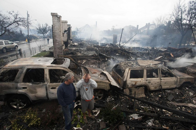 October 30, 2012: Residents look over the remains of burned homes in the Rockaways section of New York. (Keith Bedford/Reuters)