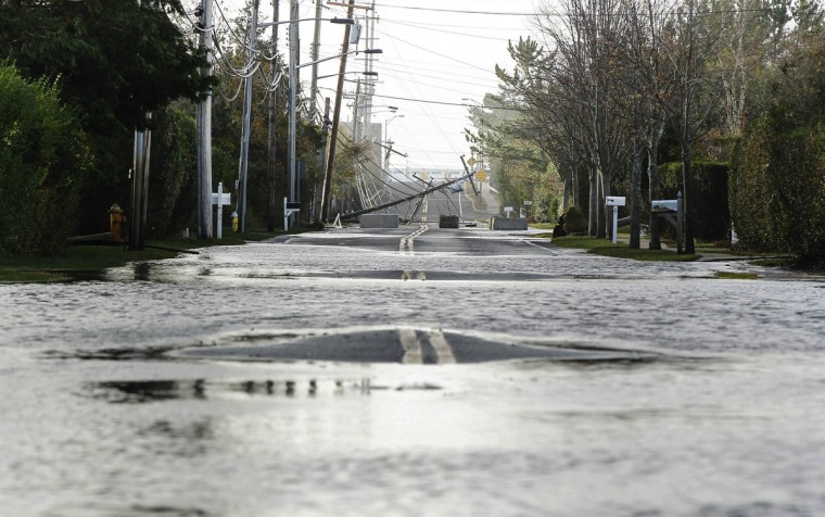 October 30, 2012: A power line lies fallen across a road flooded by floodwaters pushed up by high tide and the storm surge from Hurricane Sandy in Westhampton Beach, New York. (Lucas Jackson/Reuters)