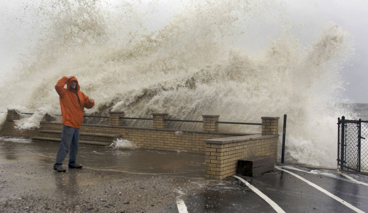 October 29, 2012: Waves crash over Eric Mongirdas as the storm surge caused by Hurricane Sandy pummels the coastline in Milford, Connecticut. (Michelle McLoughlin/Reuters)