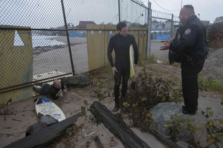 October 29, 2012: A police office questions two surfers as they climb under a fence after surfing in Coney Island in New York. (Keith Bedford/Reuters)