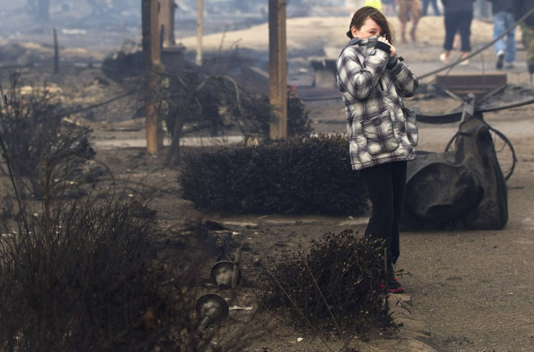 October 30, 2012: A girl stands among homes devastated by fire and the effects of Hurricane Sandy at the Breezy Point section of the Queens borough of New York. (Shannon Stapleton/Reuters)
