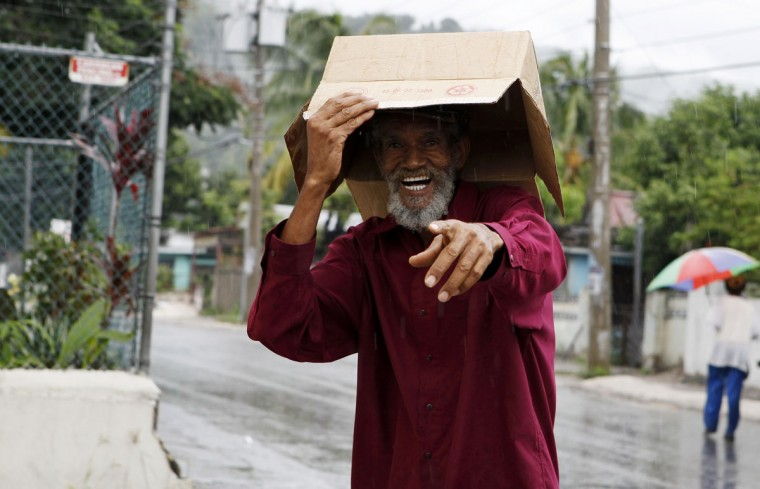 October 23, 2012: A man reacts to being photographed as he uses a box to protect him from the rain before the arrival of Tropical Storm Sandy, predicted to be a hurricane before it reaches the island on Wednesday, in Kingston. (Gilbert Bellamy/Reuters)