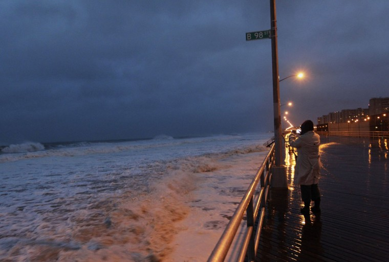 October 29, 2012: A woman takes a photo at Beach 98th street on the boardwalk at Rockaway beach in the Queens borough of New York. (Shannon Stapleton/Reuters)
