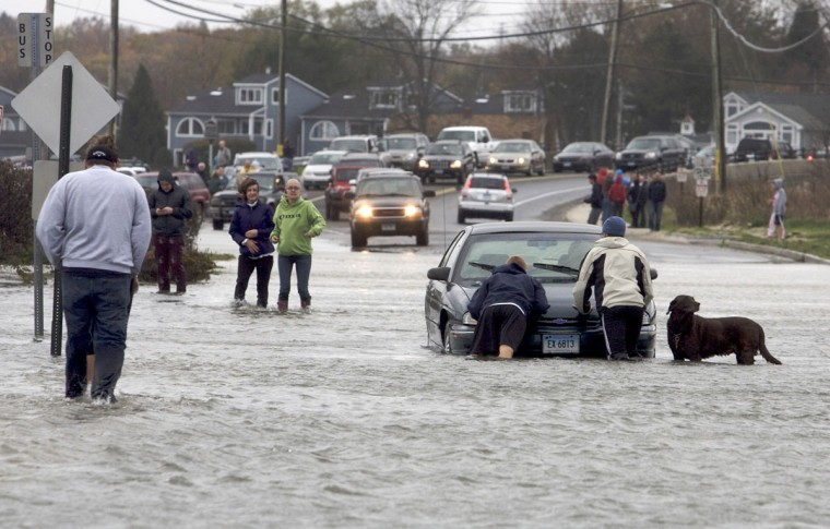 October 29, 2012: Pedestrians come to the aid of a motorist stuck on a flooded-out road along the shoreline area of Milford, Connecticut ahead of Hurricane Sandy. (Michelle McLoughlin/Reuters)